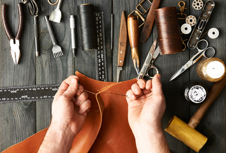 Photo pour Man working with leather using crafting DIY tools - image libre de droit