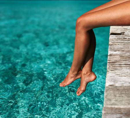 Foto de Woman relaxing at beach jetty - Imagen libre de derechos