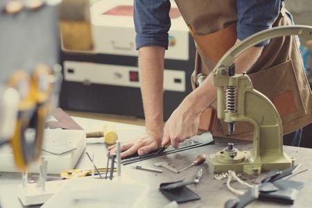Photo pour Leather craft workshop owner at his work place - image libre de droit