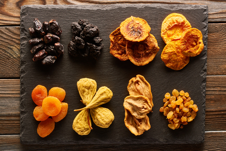 Dried fruits on slate plate over vintage rustic wooden background