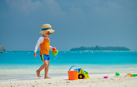 Photo pour Three year old toddler boy playing with beach toys on beach. Summer family vacation at Maldives. - image libre de droit