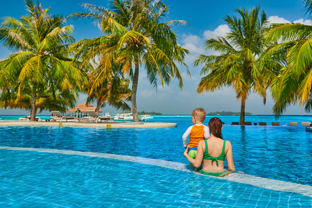 Photo pour Three year old toddler boy in resort swimming pool with mother. Summer family vacation at Maldives. - image libre de droit