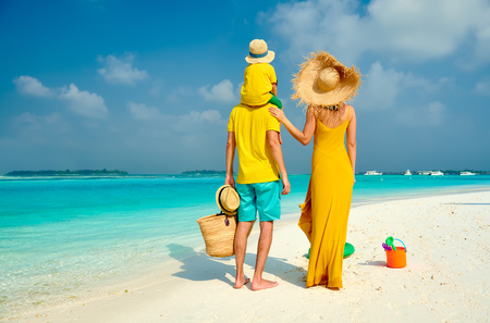 Foto per Family on beach, young couple in yellow with three year old boy. Summer vacation at Maldives. - Immagine Royalty Free