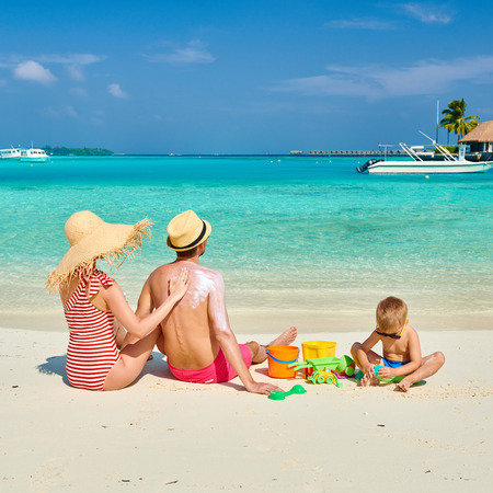 Photo for Family on beach, young couple with three year old boy. Woman applying sun screen protection lotion on man's back. Summer vacation at Maldives. - Royalty Free Image