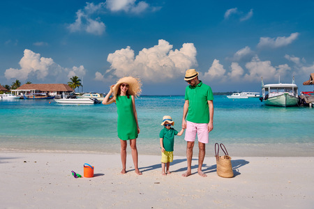 Photo for Family on beach, young couple in green with three year old boy. Summer vacation at Maldives. - Royalty Free Image