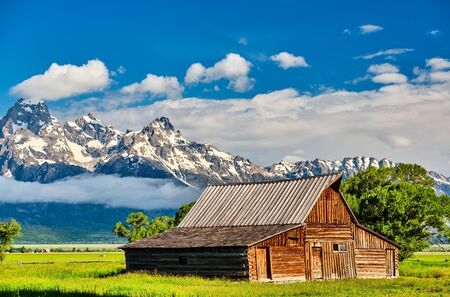 Photo pour Old mormon barn in Grand Teton Mountains with low clouds. Grand Teton National Park, Wyoming, USA. - image libre de droit