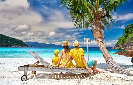 Photo for Family on beautiful Petite Anse beach, young couple with three year old toddler boy sitting on sun bed. Summer vacation at Seychelles, Mahe. - Royalty Free Image