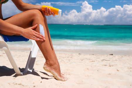 Photo for Tan woman applying sun protection lotion - Royalty Free Image
