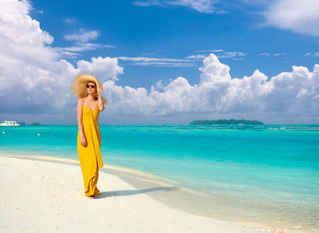 Photo pour Woman in dress walking on tropical beach. Summer vacation at Maldives. - image libre de droit