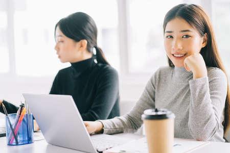 Foto de two asian business women are gathered in the office - Imagen libre de derechos