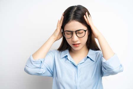 Foto de portrait of asian woman holding her head because of a headache - Imagen libre de derechos