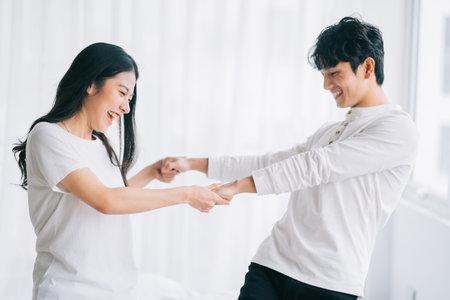 Photo pour Asian couple dancing together in the bedroom - image libre de droit