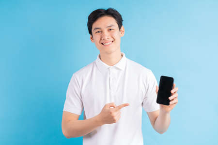 Photo pour Smiling young man holds a modern smartphone in his hand and shows his finger on a blank white screen, isolated on a blue background. - image libre de droit