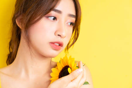 Photo for Beautiful Asian woman holding and posing with sunflower on yellow background - Royalty Free Image