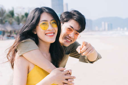 Photo pour Young Asian couple enjoying summer vacation on the beach - image libre de droit