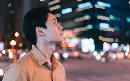 Photo pour Asian man is walking in the street at night feeling lost - image libre de droit