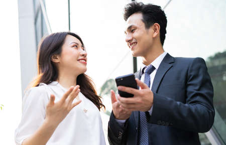 Photo pour Two Asian business people using smartphone and talking together - image libre de droit