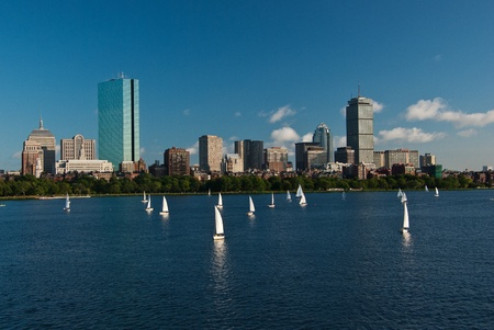 A view of Boston Massachusetts across the Charles River with sailboats in the foreground during a late summer afternoon