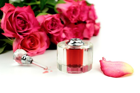 Perfume and roses on white background