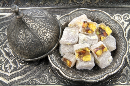 Turkish delight with pistachio nuts in traditional carved patterned metal plate