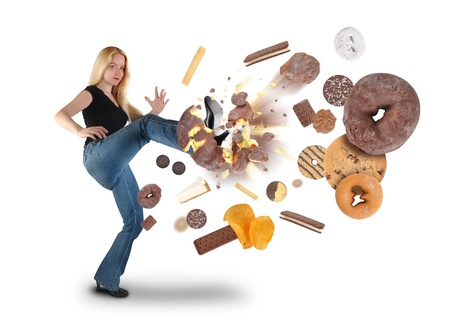 A young woman is kicking a donut on a white background within an assortment of junk food  There are cookies, chips and ice cream  Use it for a diet or nutrition concept