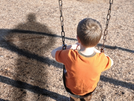 A young boy is sitting on a swing set and looking at a shadow figure of a man or bully at a playground  Use it for a kidnap or defense concept