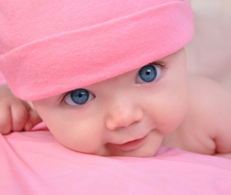 A cute little baby girl is staring up and is on a pink blanket  She is wearing a pink hat and has big blue eyes  Use it for a child, parenting or love concept