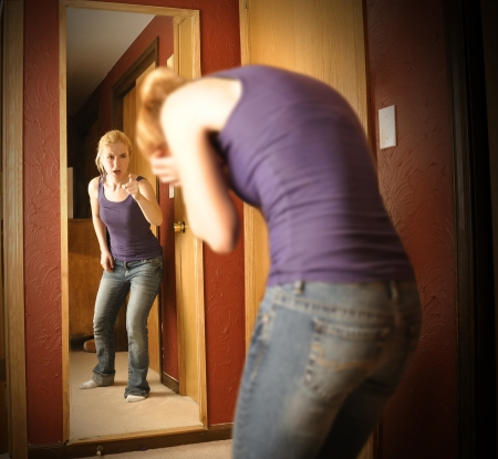 A young woman is depressed looking in a mirror while the reflection is yelling an pointing at her self in anger.