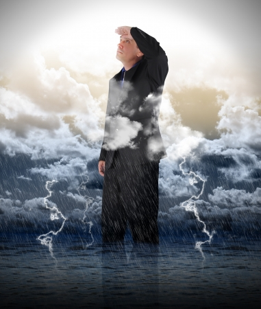 A business man is looking up to bright light in stormy weather for a strength, success or faith metaphore