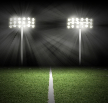 Two Stadium football game lights are shinning on a green grass field for a sport concept.