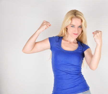 A happy beautiful girl is holding up her strong muscles on an isolated background to show confidence and strengh.