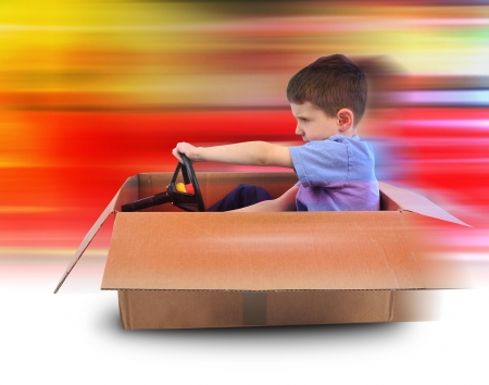 A young boy is driving in a cardboard box with red speed lines in the background