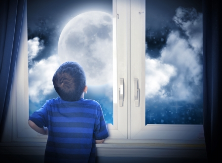 A young boy is looking out of the window at a big moon in the dark night with stars and space for an astronomy or imagaination concept