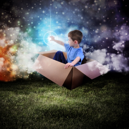 A young boy is sitting in a cardboard box and floating in the night sky reaching for a star in space.