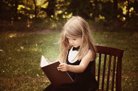A smart little girl is reading an old book in nature with trees in the background for an education or knowledge concept