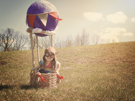 A little girl is sitting in a hot air balloon pretending to be a pilot flying on a grass field for an imagination or travel concept.