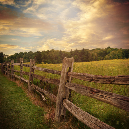 An old rustic wooden fence is in a grass filed with trees and clouds in the background for a country or nature concept.