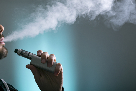 Photo pour young man vape electronic cigarette cloud by using a mod, smoke tricks of vaping device background. - image libre de droit