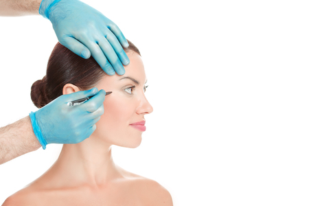 Foto de Anti wrinkle procedure. Crow-feet wrinkles reduction removal plastic surgery cosmetic filling operation concept. Doctor surgeon hand in gloves draw wrinkle line on Woman isolated white background. - Imagen libre de derechos