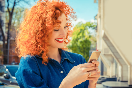Photo for Young beautiful red curly hair woman, smiling, looking her mobile phone texting, reading sms message. Isolated city on background. Positive human emotions face expression feelings. - Royalty Free Image