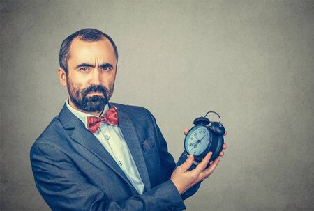 Photo pour Closeup portrait serious adult bearded man in elegant jacket with red bow tie holding showing alarm clock in his hands looking at you camera, gray wall background. Human face expression, body language - image libre de droit