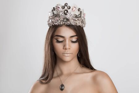 Photo pour Trendy style makeup. Closeup portrait crowned brunette woman face with beautiful shiny makeup eyes closed on white grey background wall. Dark skin beauty queen, thick eye brows, brown long hair, crown - image libre de droit