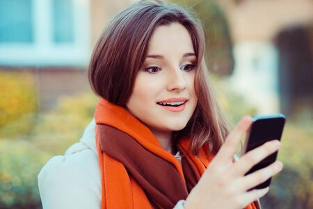 Photo for wow, good news on screen. Closeup surprised screaming young girl looking at phone seeing new photos with funny emotion on her face isolated outside city background. Human emotion, reaction, expression - Royalty Free Image