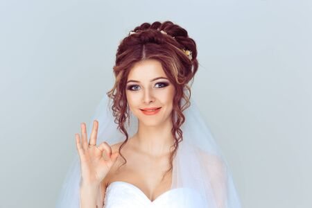 Photo for Portrait beautiful happy young woman showing Ok sign with hand isolated on light blue wall background. Positive human emotions face expression body language - Royalty Free Image