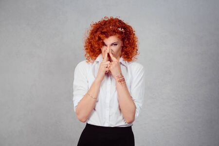 Photo pour Stinky. Closeup portrait young red head business woman pinches her nose with fingers looks with disgust something stinks bad smell isolated gray wall background. Face expression body language reaction - image libre de droit