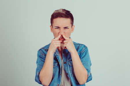 Photo pour headshot woman pinches nose with fingers hand looks with disgust away something stinks bad smell situation isolated on gray green wall background. Human face expression body language reaction - image libre de droit