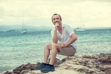 Photo pour Smiling man sitting on the seashore coast by the sea, toothy smile middle age man multicultural mixed race, outdoors - image libre de droit