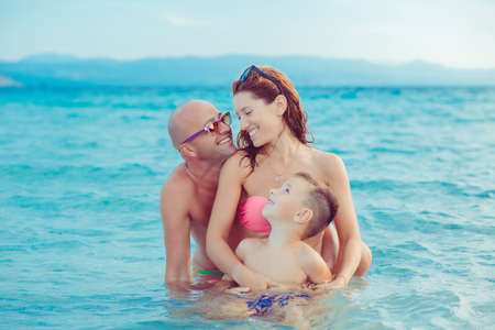 Photo pour Cute Family on the beach having fun together outdoors, blue sea water on background - image libre de droit