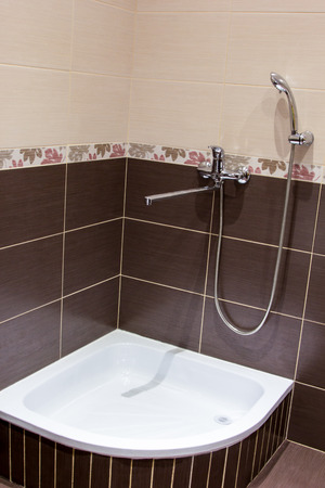 shower tray in the bathroom lined with brown tiles