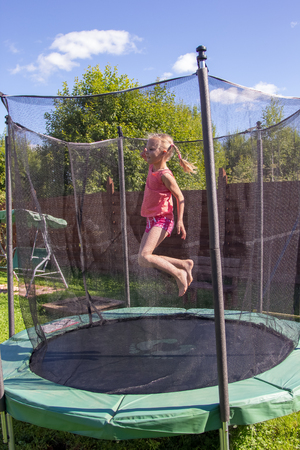 Photo pour girl jumping on a trampoline behind a protective net - image libre de droit